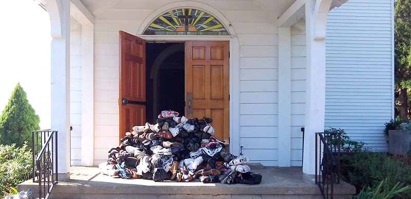 photo of church with pile of recycled shoes on it's doorstep