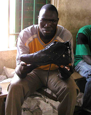 photo of African man holding shoe